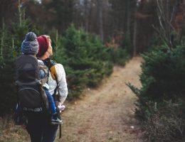 Madre cargando a su hijo en la espalda mientras camina en el bosque