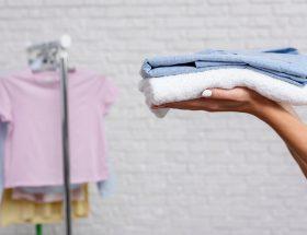 Manos de mujer con ropa doblada en sus palmas