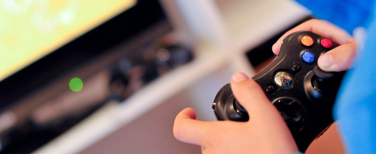 Niño con sudadera azul jugando videojuegos con control remoto en su mano