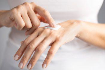 Mujer humectando sus manos