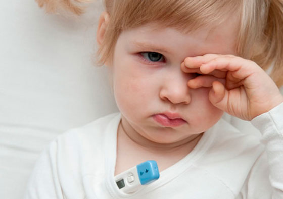 niña con termometro checando su temperatura