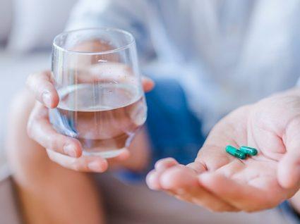 persona tomando medicamentos con vaso de agua
